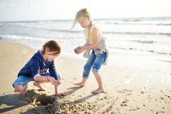 Two little sisters having fun on a sandy beach on warm and sunny summer day. Kids playing by the ocean. Stock Image