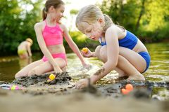 Two little sisters having fun on a sandy lake beach on warm and sunny summer day. Kids playing by the river stock photography