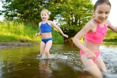 Two little sisters having fun on a sandy lake beach on warm and sunny summer day. Kids playing by the river stock photos