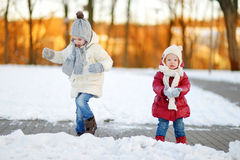 Two little sisters having fun on snowy winter day Stock Image
