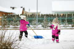 Two little sisters having fun on snowy winter day Stock Photo