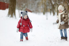 Two little sisters having fun on snowy winter day Stock Photos