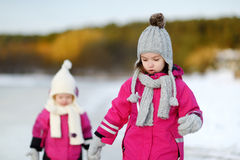 Two little sisters having fun on snowy winter day Stock Images