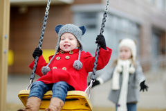 Two little sisters having fun on a swing Stock Image