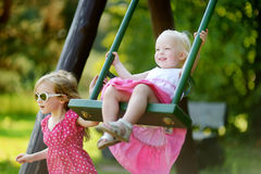 Two little sisters having fun on a swing Stock Images