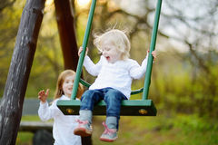 Two little sisters having fun on a swing Royalty Free Stock Image