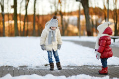 Two little sisters having fun on winter day Stock Images