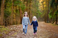 Two little sisters having fun in the woods Stock Photos