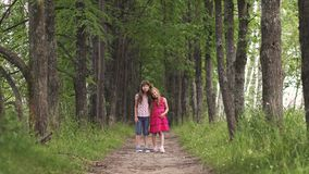 Two little sisters holding hands and cuddling. children`s friendship. Two little girls hold hands and walk down the green alley. children walk outdoors. two stock video