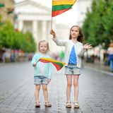 Two little sisters holding Lithuanian flags in Vilnius Royalty Free Stock Images