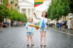Two little sisters holding Lithuanian flags in Vilnius stock photo
