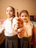 Two little sisters holding red pencil Stock Photos