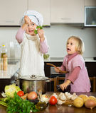 Two little sisters at home kitchen Royalty Free Stock Images