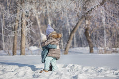 Two little sisters hug each other in snow in winter Stock Image
