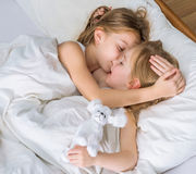 Two little sisters hugging in bed Royalty Free Stock Photography