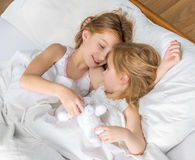 Two little sisters hugging in bed Royalty Free Stock Photo