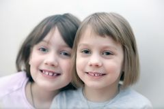Portrait of two pretty girls. Two little sisters   hugging at home stock image