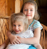 Two little sisters hugging. Little sisters sitting embracing each other at home Stock Images