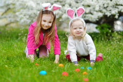 Two little sisters hunting for easter egg on Easter day Royalty Free Stock Photos