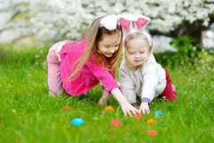 Two little sisters hunting for easter egg on Easter day Stock Photos