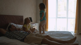Two little sisters jumping on the bed and having fun Stock Photography