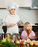 Two little sisters learning how to cook Stock Photo