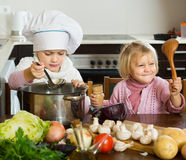 Two little sisters learning how to cook Royalty Free Stock Images