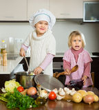 Two little sisters learning how to cook Stock Photos