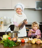 Two little sisters learning how to cook Royalty Free Stock Image