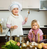 Two little sisters learning how to cook Royalty Free Stock Photos