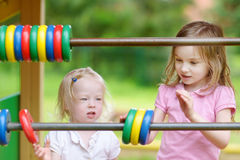 Two little sisters learning to count. At a playground royalty free stock image