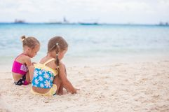 Two little sisters in nice swimsuits playing on Stock Image