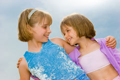 Two little sisters over blue sky. Two cute little sisters over blue sky Royalty Free Stock Photos