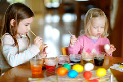 Two little sisters painting colorful Easter eggs Stock Images