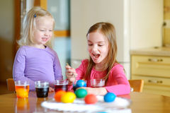 Two little sisters painting colorful Easter eggs Royalty Free Stock Photography