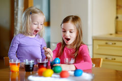 Two little sisters painting colorful Easter eggs Royalty Free Stock Photos