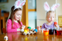 Two little sisters painting colorful Easter eggs Stock Image