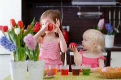 Two little sisters painting Easter eggs Stock Photography