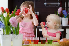 Two little sisters painting Easter eggs Stock Image
