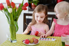 Two little sisters painting Easter eggs Royalty Free Stock Photography