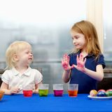 Two little sisters painting Easter eggs Royalty Free Stock Images