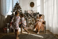 Two little sisters in pajamas having fun New Year`s tree with gifts in the light cozy room and their mother sits in the royalty free stock images