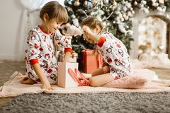 Two little sisters in pajamas sit on the carpet and open New Yea