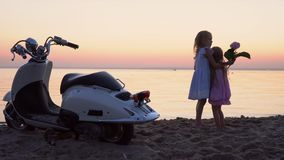 Two little sisters are photographed at the white moped on the seashore. Two little fair-haired girls pose for the camera. On this video you can see as the close stock footage