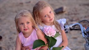 Two little sisters are photographed at the white moped on the seashore. Two little fair-haired girls pose for the camera. On this video you can see as the close stock video