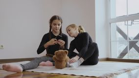 Two little sisters photographs teddy bear. Two little sisters sits on the floor in the room near the window and relaxing. Cute children plays with phone and stock video footage