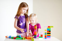 Two little sisters plaing with colorful blocks Royalty Free Stock Photography