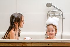 Two little sisters play in a bath. Two little sisters play in a bath with foam. They are very cheerful and lovely Royalty Free Stock Photo