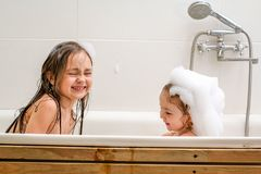 Two little sisters play in a bath. Two little sisters play in a bath with foam. They are very cheerful and lovely Stock Photos