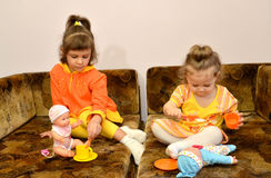Two little sisters play with dolls on a sofa.  Royalty Free Stock Image
